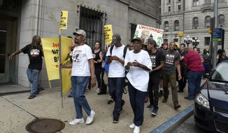 Protesters march east on Lexington Street near the courthouse in Baltimore, where they rallied during court proceedings Thursday, Sept. 10, 2015, in the Freddie Gray case. (Barbara Haddock Taylor/Baltimore Sun via AP) ** FILE **