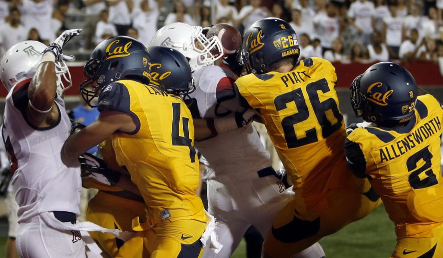 FILE - In this Sept. 20, 2014, file photo, Arizona running back Austin Hill, center in white, catches a pass for a touchdown in the middle of  California defenders including Kenny Lawler (4), Griffin Piatt (26) and Darius Allensworth (2) with no time left on the clock at Arizona Stadium in Tucson, Ariz. Anu Solomon hit Hill with the 47-yard Hail Mary to send the stunned Bears to a 49-45 loss. Of the 12 long, end-of-the-game winning touchdown passes in major-college football since 2000, five have involved Big Ten teams(AP Photo/Arizona Daily Star, Kelly Presnell, File )  ALL LOCAL TELEVISION OUT; PAC-12 OUT; MANDATORY CREDIT