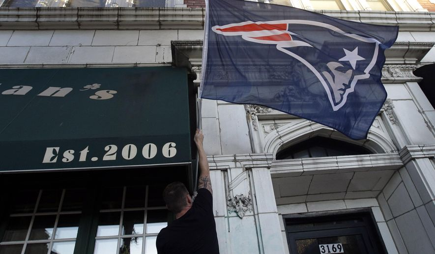 Michael Simoneau, of Chicago, hangs a New England Patriots' flag at Brendan's Pub before an NFL football game between the Pittsburgh Steelers and the Patriots on Thursday, Sept. 10, 2015, in Chicago. Friends who are Patriots fans are coming to town, and you need to find a sports bar where they will not get booed out of the joint when glamour-boy quarterback Tom Brady gets rolling. (AP Photo/Nam Y. Huh)