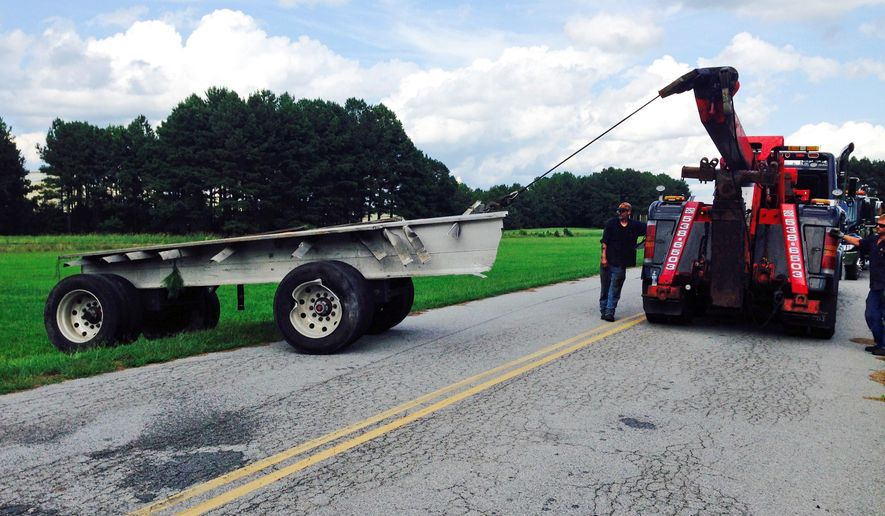 Tow truck operators remove part of a tractor-trailer that was hit by an Amtrak train at a railroad crossing, Thursday, Sept, 10, 2015 near Skippers, Va. The train was traveling north into Virginia just across the North Carolina border Thursday afternoon when the accident occurred. Neither the truck driver nor any of the 267 passengers on the train were injured.  (AP Photo/Alan Suderman)