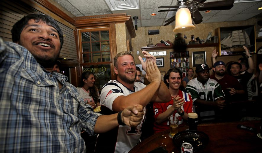 From left to right, New England Patriots fans Rishi Pentyala, of Dallas, Sean Strumm, of Boston, and Zach Regan, also of Boston, celebrate after Patriots scored a touchdown during the second quarter as they watch a big screen at Brendan's Pub during an NFL football game against the Pittsburgh Steelers, Thursday, Sept. 10, 2015, in Chicago. (AP Photo/Nam Y. Huh)
