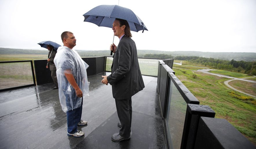 Somerset County coroner Wally Miller, center, who was in charge of recovering and identifying the remains of the 40 passengers and crew of United Flight 93, stands on the overlook of the Flight 93 National Memorial Visitor Center after attending the dedication in Shanksville, Pa., Thursday, Sept. 10, 2015. Sitting on a hill overlooking the crash site near Shanksville, the $26 million visitor center complex opened to the public on Thursday, one day before the annual 9/11 observances in Pennsylvania, New York and Washington. (AP Photo/Gene J. Puskar)