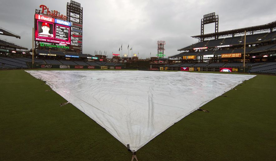 The field is covered as rain falls prior to a baseball game between the Philadelphia Phillies and the Chicago Cubs, Thursday, Sept. 10, 2015, in Philadelphia. (AP Photo/Chris Szagola)