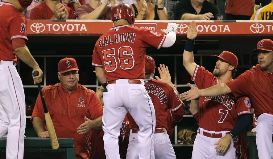 Los Angeles Angels' Kole Calhoun, center, is greeted by teammates and coaches after hitting a sacrifice fly during the third inning of a baseball game against the Los Angeles Dodgers, Wednesday, Sept. 9, 2015, in Anaheim, Calif. (AP Photo/Jae C. Hong)