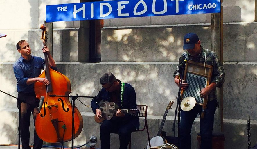 This Aug. 25, 2015 photo shows Devil in a Woodpile, a rootsy jug band-like group, performing at The Hideout's outpost along Chicago's Riverwalk. The spot is an upscale version of the Hideout's  beloved music venue and bar's divey Northwest Side location, and offers al fresco free music and cheap drinks until Nov. 1. (AP Photo/Lindsey Tanner)