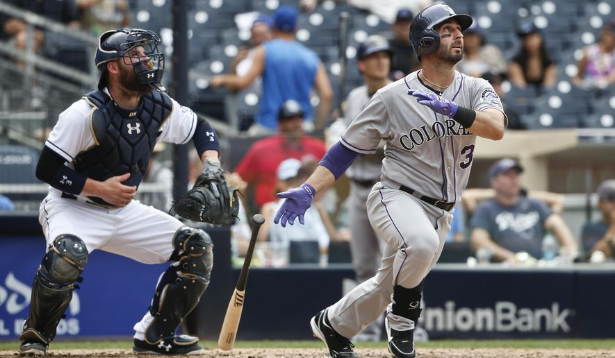 Colorado Rockies' Daniel Descalso, right, and San Diego Padres catcher Austin Hedges follow the flight of Descalso's solo home run in the eighth inning of a baseball game Thursday, Sept. 10, 2015, in San Diego. (AP Photo/Lenny Ignelzi)