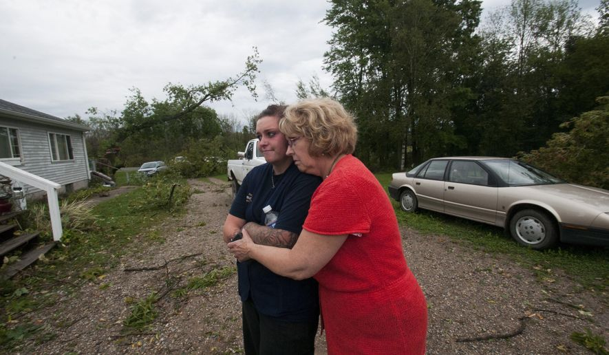 Courtney Oakes is hugged by her grandmother, Carol Riker, as they look at the fallen trees around her house after a possible tornado passed the area in Rose City, Mich., on Tuesday, Sept. 8, 2015.  The National Weather Service plans to survey damage on Wednesday to determine whether it was caused by a tornado or straight-line winds. (Nicole Hester /The Bay City Times via AP) LOCAL TELEVISION OUT; LOCAL INTERNET OUT; MANDATORY CREDIT