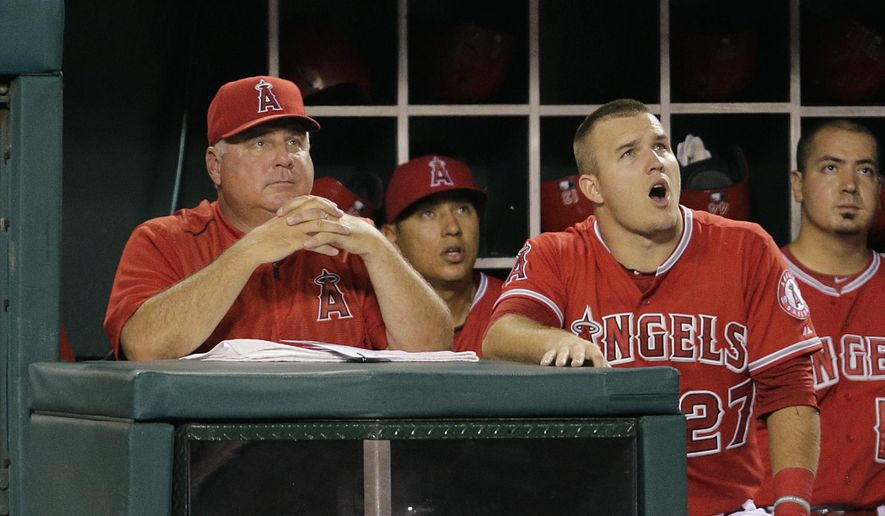 Los Angeles Angels manager Mike Scioscia, left, and player Mike Trout, right, watch a foul ball hit by Carlos Perez during the second inning of a baseball game against the Los Angeles Dodgers, Wednesday, Sept. 9, 2015, in Anaheim, Calif. (AP Photo/Jae C. Hong)