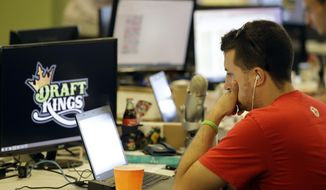 In this Wednesday, Sept. 9, 2015, photo, Devlin D'Zmura, a tending news manager at DraftKings, a daily fantasy sports company, works on his laptop at the company's offices in Boston. The daily fantasy sports industry is eyeing a breakout season as NFL games begin. And its two dominant companies, DraftKings and FanDuel, are touting lucrative opening week prizes to try to draw more customers as more competitors pop up. (AP Photo/Stephan Savoia) ** FILE **