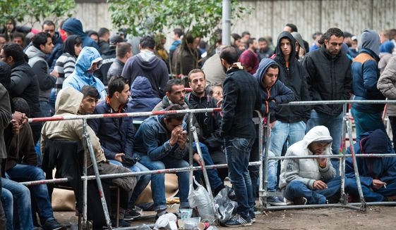 Refugees and migrants wait outside the Berlin State Office for Health and Social Affairs in Berlin, Germany, Friday Sept. 11,  2015. Every day, hundreds of asylum seekers wait here to be registered. (Bernd von Jutrczenka/dpa via AP)
