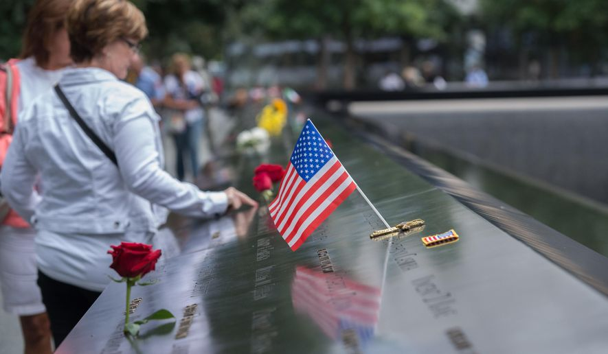 Visitors touch the names of the victims of the Sept. 11 terror attacks at the South Pool of the National September 11 Memorial on Friday, Sept. 11, 2015 in New York.  With a moment of silence and somber reading of names, victims' relatives began marking the 14th anniversary of Sept. 11 in a subdued gathering Friday at ground zero. (AP Photo/Bryan R. Smith)