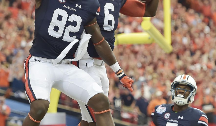 FILE - In this Sept. 5, 2015, file phtoo, Auburn quarterback Jeremy Johnson (6) celebrates his touchdown with Auburn wide receiver Melvin Ray (82) during the first half of an NCAA college football game against Louisville in Atlanta. (AP Photo/Mike Stewart, File)