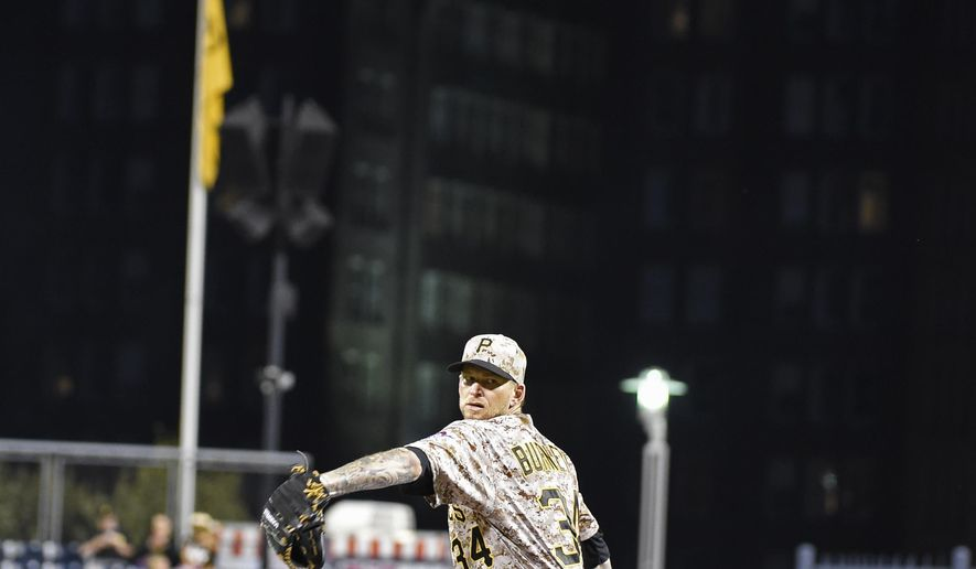 Pittsburgh Pirates' A.J. Burnett throws a pitch to Milwaukee Brewers' Domingo Santana in the fourth inning of a baseball game, Thursday, Sept. 10, 2015, in Pittsburgh. A Batman logo, top, wa displayed on a downtown Pittsburgh building in honor of Burnett's return to the rotation. (AP Photo/Fred Vuich)