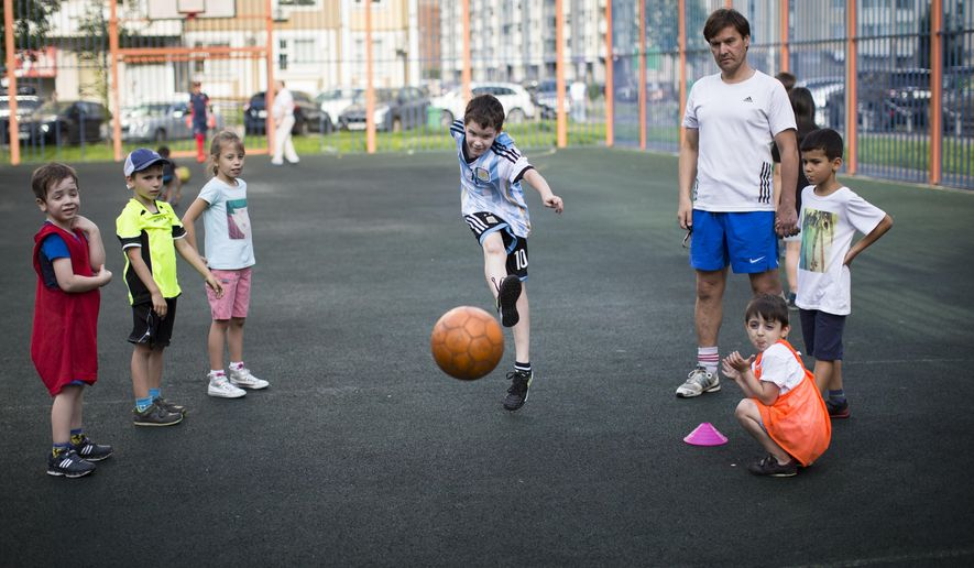 In this photo taken on Sunday, July  5, 2015, coach Andrei Ilayskin watches as children learn to take a penalty  at a playground in one of the  yards, between tower blocks, in Moscow Russia. Preparing to host the 2018 World Cup, Russia already looks to a future generation of soccer stars and government-funded programs to provide free coaching give kids the chance to learn the basics of the game for free. (AP Photo/Alexander Zemlianichenko)