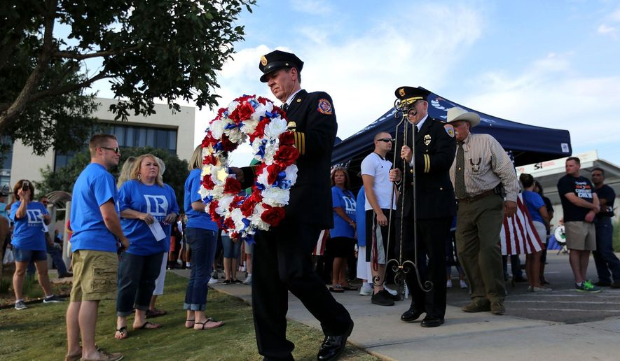 "Odessa Fire/Rescue Chief Roger Boyd, center, Odessa Police Chief Tim Burton and Ector County Sheriff Mark Donaldson walk to place a wreath in honor of the first responders who died in the line of duty in Odessa and Ector County during the 13th Annual ""American Tribute"" ceremony Thursday Sept. 10, 2015 at the Memorial Gardens Park in Odessa, Texas. The ceremony pays a tribute to those who lost their lives during the terrorist attacks on Sept. 11, 2001 by placing 3,000 flags around the pond. (Edyta Blaszczyk/Odessa American via AP) MANDATORY CREDIT"