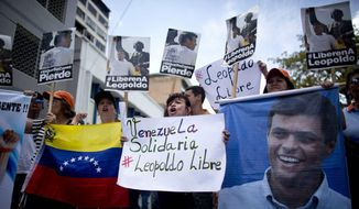 People chant slogans in support of jailed opposition leader Leopoldo Lopez, outside the courthouse in Caracas, Venezuela, Thursday, Sept. 10, 2015. Members of Lopez's party arrived early in the morning to protest and pray, as they have dozens of times since Lopez's imprisonment 19 months ago. Lopez is accused of fomenting violence during a 2014 protest movement, and a verdict could come soon. (AP Photo/Ariana Cubillos) ** FILE **