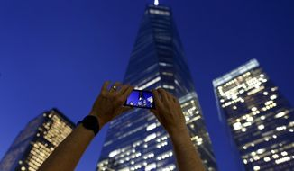 A visitor to the National September 11 memorial, pans his phone while shooting video of One World Trade Center and surrounding buildings on the 13th anniversary of the attacks on the World Trade Center in New York on Sept. 11, 2014. (Associated Press)