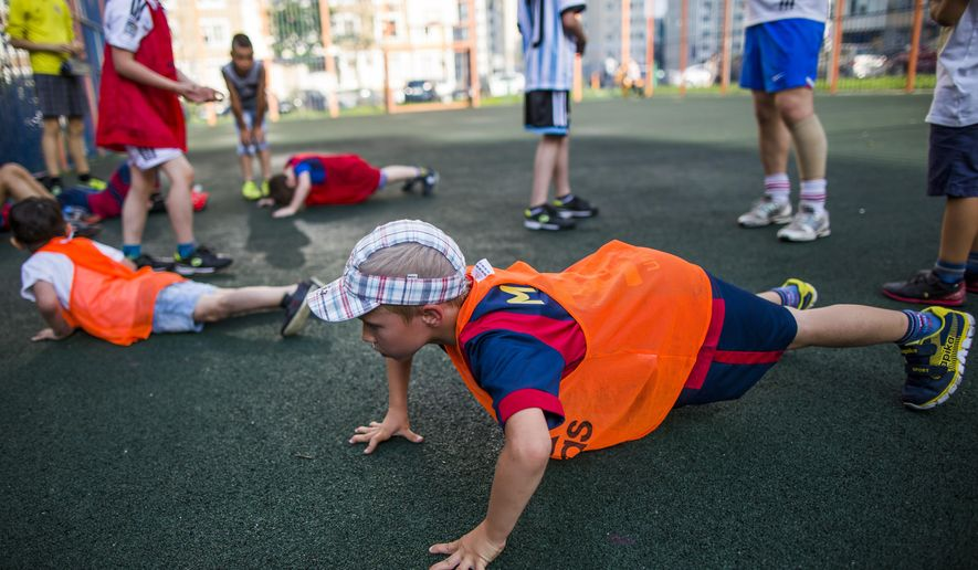 In this photo taken on Sunday, July  5, 2015, young football players exercise during a training session at a playground in one of  the yards, between tower blocks, in Moscow Russia. Preparing to host the 2018 World Cup, Russia already looks to a future generation of soccer stars and government-funded programs to provide free coaching give kids the chance to learn the basics of the game for free. (AP Photo/Alexander Zemlianichenko)
