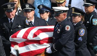 The casket of slain Fox Lake police Lt. Charles Joseph Gliniewicz is loaded into the hearse at Antioch Community High School, in Antioch, Ill., in this Sept. 7, 2015, file photo. (Stacey Wescott/Chicago Tribune via AP, File)