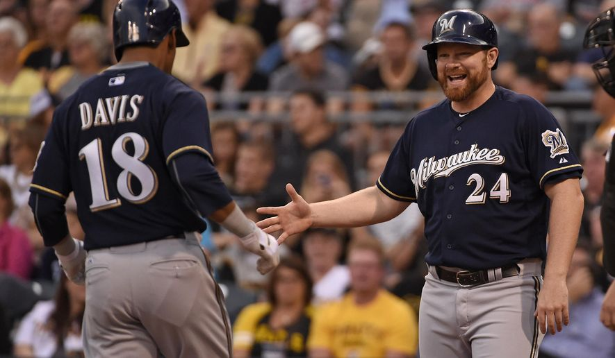 Milwaukee Brewers' Khris Davis, left, is greeted at home plate by teammate Adam Lind after hitting a two-run home run off Pittsburgh Pirates' pitcher A.J. Burnett in the first inning of a baseball game, Thursday, Sept. 10, 2015, in Pittsburgh. (AP Photo/Fred Vuich)