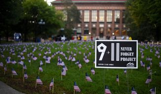 2,977 small American flags were placed in the ground as part of the 9/11 Never Forget Project memorial at the Diag at the University of Michigan in Ann Arbor, Mich., on Friday, Sept. 11, 2015.  (Melanie Maxwell /The Ann Arbor News via AP) LOCAL TELEVISION OUT; LOCAL INTERNET OUT; MANDATORY CREDIT