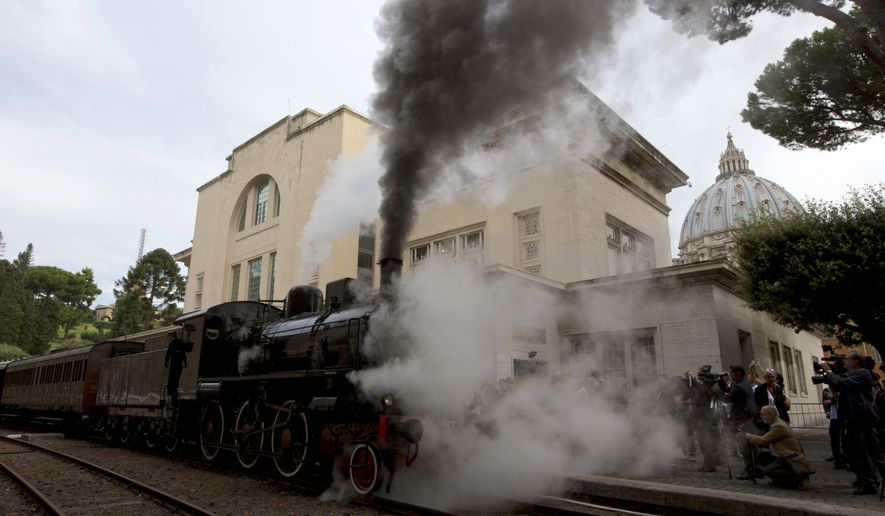 Smoke billows from a steam locomotive as the dome of St. Peter's Basilica stands out in background right, before its departure from the Vatican's train station, Friday, Sept. 11, 2015. With a deafening whistle and a plume of smoke, an antique train departed from the Vatican rail station Friday to inaugurate a weekly train service to the papal summer estate in Castel Gandolfo now that Pope Francis has decided to open it to the public. (AP Photo/Alessandra Tarantino)