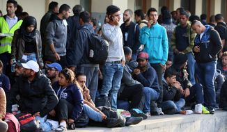 Migrants and refugees wait for a train from Vienna to Munich at the Westbahnhof train station in Vienna, Thursday, Sept. 10, 2015. (AP Photo/Ronald Zak)