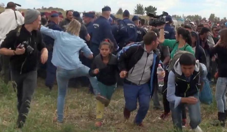 In this image taken from TV a Hungarian camerawoman, center left in blue, kicks out at a young migrant who had just crossed the border from Serbia near Roszke Hungary Tuesday, Sept. 8, 2015. The camerawoman has been fired after she was caught on video kicking and tripping migrants entering Hungary across the border with Serbia. (Index.Hu. via AP)