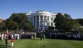 "President Barack Obama, first lady Michelle Obama, and others, stand on the South Lawn of the White House in Washington, Friday, Sept. 11, 2015, as a bugler plays ""Taps"" during a ceremony to observe the 14th anniversary of the 9/11 terrorists attacks. (AP Photo/Evan Vucci)"