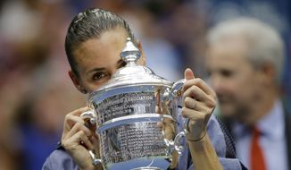 Flavia Pennetta, of Italy, kisses the championship trophy after beating Roberta Vinci, of Italy, in the women's championship match of the U.S. Open tennis tournament, Saturday, Sept. 12, 2015, in New York. (AP Photo/David Goldman)