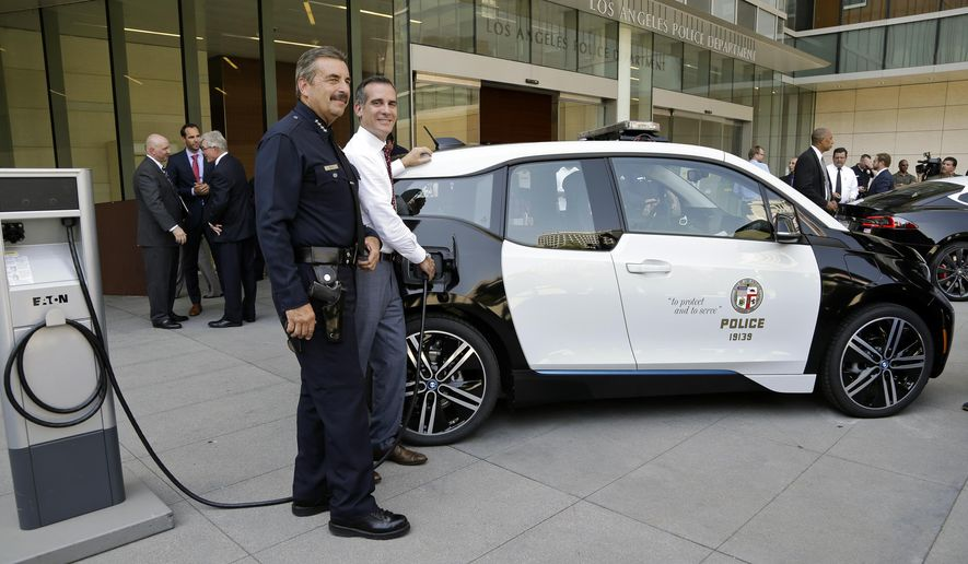 Los Angeles Police Chief Charlie Beck, left, and Mayor Eric Garcetti pose next to an all-electric car after a news conference announcing the city's transition to green energy vehicles for its fleet purchase, outside the Police Administration Building in Los Angeles on Friday, Sept. 11, 2015. (AP Photo/Nick Ut)