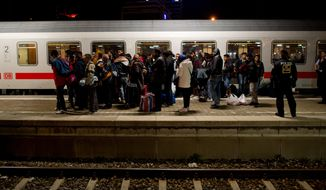 Refugees and migrants wait on a platform for a special train that will take them to Dortmund in western Germany at the central station in Munich on Sept. 13, 2015. (Associated Press)