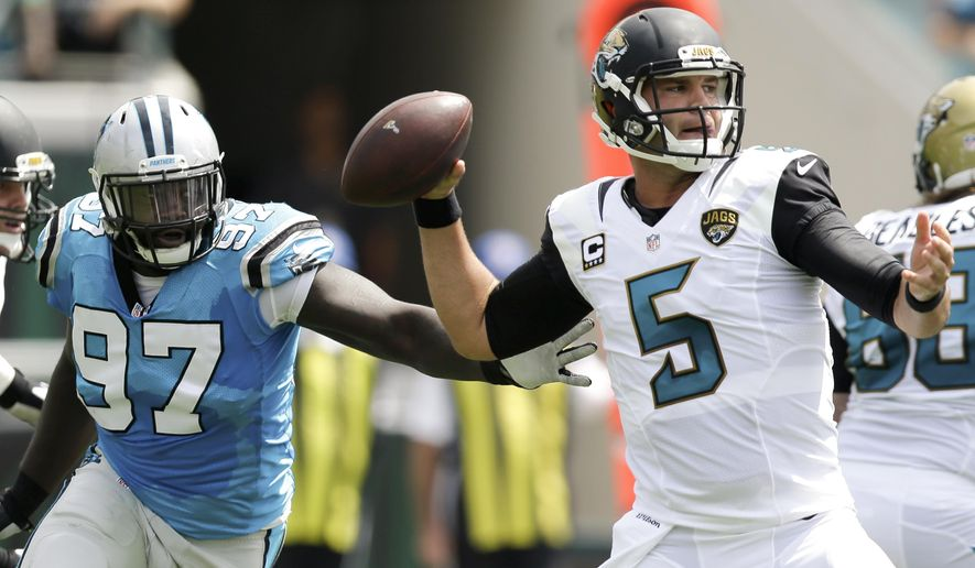 Jacksonville Jaguars quarterback Blake Bortles (5) looks for a receiver as Carolina Panthers defensive end Mario Addison (97) puts on pressure during the first half of an NFL football game in Jacksonville, Fla., Sunday, Sept. 13, 2015. (AP Photo/John Raoux)