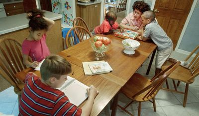 Diane Toler, director of the Catholic Homeschoolers of New Jersey, plays a game to help improve the math skills of her sons, John, 6, (right) and Michael, 4, as another son, Joshua, 10, left, and daughter, Alexandra, 8, work on a writing assignment at their home in Cherry Hill, N.J. (Associated Press)
