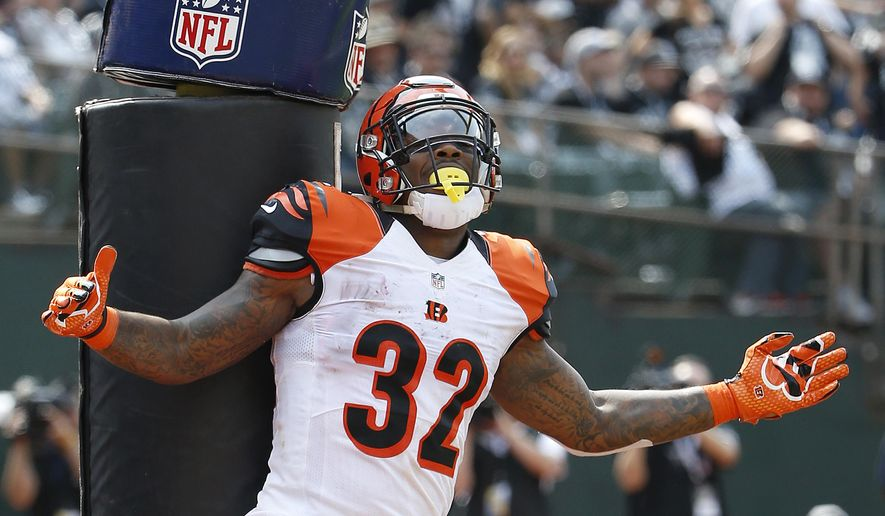 Cincinnati Bengals running back Jeremy Hill (32) celebrates after scoring on a 2-yard touchdown run against the Oakland Raiders during the first half of an NFL football game in Oakland, Calif., Sunday, Sept. 13, 2015. (AP Photo/Tony Avelar)