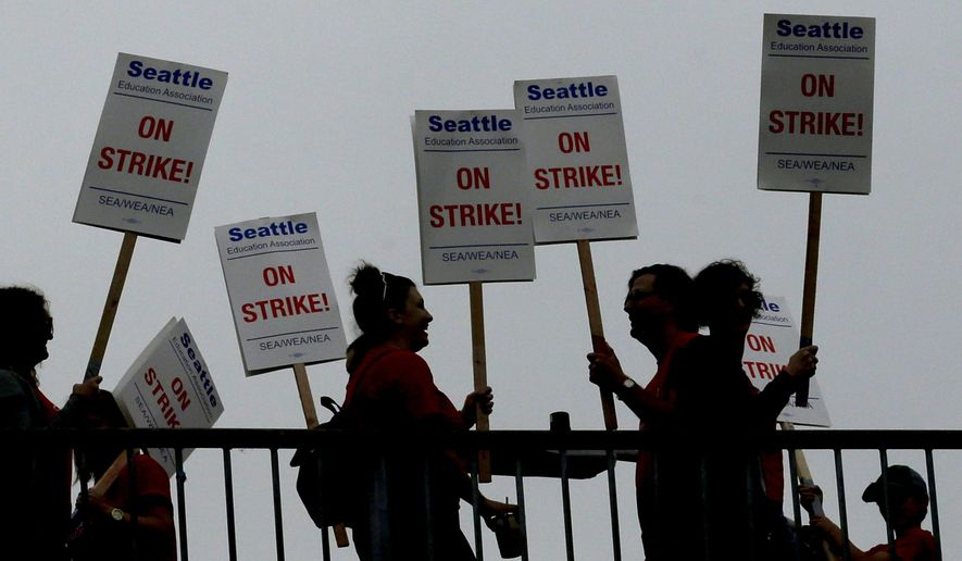 FILE - In this Sept. 10, 2015, file photo, striking Seattle School District teachers and other educators walk a picket line on a pedestrian overpass near Franklin High School in Seattle. The city opened more of its community centers Monday, Sept. 14, 2015, to help Seattle parents who were scrambling for child care as a teacher strike entered its fourth day. Several of the centers quickly filled, forcing them to turn families away. (AP Photo/Ted S. Warren, File)