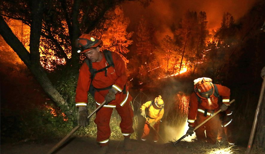 Firefighters create a firebreak near a home in Middletown, Calif., on Sunday, Sept. 13, 2015. Two of California's fastest-burning wildfires in decades overtook several Northern California towns, killing at least one person and destroying hundreds of homes and businesses. (AP Photo/Elaine Thompson)