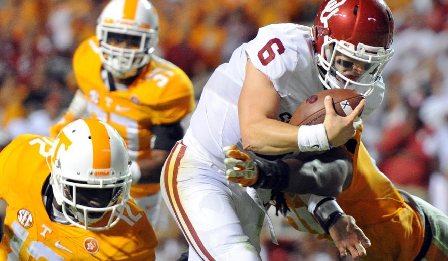 FILE - In this Saturday, Sept. 12, 2015, file photo, Oklahoma quarterback Baker Mayfield (6) beats a tackle by Tennessee defensive back Emmanuel Moseley (12) to score a touchdown in the first overtime of an NCAA college football game  in Knoxville, Tenn. For years, Mayfield dreamed of creating dramatic victories for the Sooners. After a 17-point comeback against Tennessee, those heroics are now real for the walk-on.  (Adam Lau/Knoxville News Sentinel via AP, File) MANDATORY CREDIT