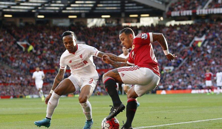 Manchester United's Memphis Depay, right, is challenged by Liverpool's Nathaniel Clyne during the English Premier League soccer match between Manchester United and Liverpool at Old Trafford Stadium, Manchester, England, Saturday, Sept. 12, 2015. (AP Photo/Jon Super)