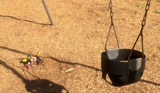 In this photo taken May 26, 2015, a stuffed animal and flowers sit near a swing in Wills Memorial Park in LaPlata, Md. A Maryland woman was found pushing her dead son in a playground swing earlier this year. (AP Photo/Matthew Barakat) ** FILE **