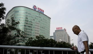 A man checks his mobile phone as he walks by buildings of China's state-owned companies, China National Offshore Oil Corp. (CNOOC), left, and China Petroleum & Chemical Corp. (Sinopec), in Beijing Monday, Sept. 14, 2015. China's Communist Party has issued a long-awaited blueprint for overhauling bloated state industries that retains the party's dominance in the economy. (AP Photo/Andy Wong)