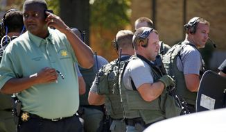 Law enforcement officers gather on the Delta State University campus to search for an active shooter in connection with a the shooting of history professor Ethan Schmidt in his office at at Delta State University in Cleveland, Miss., Monday. (Associated Press)