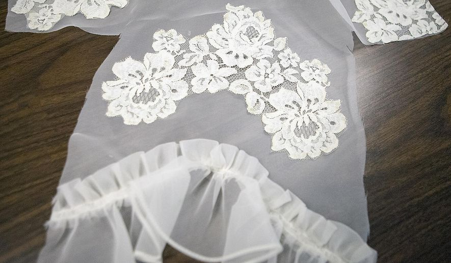 In this Aug. 31, 2015, photo, a used wedding dress that has been cut into pieces is laid out and prepared to be turned into an infant burial gown at the First Presbyterian Church in Galesburg, Ill. Members of the AN Chapter of the Philanthropic Educational Organization (PEO) club meet once a month to create the gowns after discovering there is a need for the burial gowns. (Steve Davis/The Register-Mail via AP)