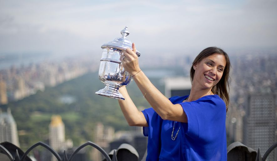 Flavia Pennetta, of Italy, holds the U.S. Open tennis women's singles championship trophy during a visit to the Top of the Rock Observation Deck at Rockefeller Center, Sunday, Sept. 13, 2015, in New York. (AP Photo/David Goldman)