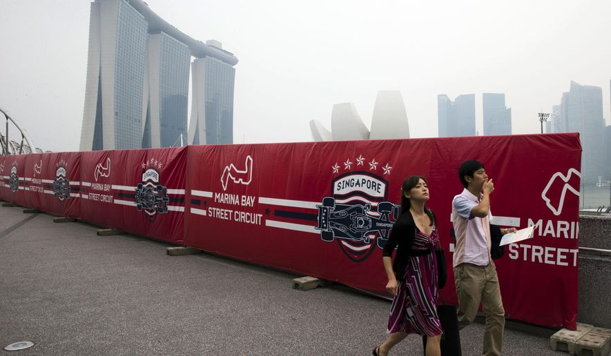Tourists walk past advertisements promoting the upcoming Singapore Formula One Grand Prix on a hazy day in Singapore, Monday, Sept. 14, 2015. Billowing smoke from Indonesian forest fires worsened Singapore's air pollution, raising concern among organizers of the widely-anticipated F1 night race this weekend, as well as in schools which reopened Monday after a weeklong term break. (AP Photo/Ng Han Guan)