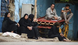 Relatives of an Egyptian victim who was killed in Sunday's incident in which Egyptian forces mistakenly opened fire on tourists in the western desert, wait at a morgue in Cairo, Egypt, Monday, Sept. 14, 2015. Egyptian forces hunting militants in the country's western desert mistakenly opened fire on Mexican tourists on safari, killing 12 people and dealing a further blow to the government's efforts to project an image of stability as it fights an increasingly powerful insurgency, officials said Monday. (AP Photo/Mohamed Elraai)