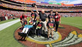 This handout photo provided by the Office of the Governor, taken Sept. 13, 2015, shows Maryland Gov. Larry Hogan, center,  attending the Washington Redskins home opener against the Miami Dolphins, in Landover, Md., along with four children from the Cool Kids Campaign, who are also battling cancer. (Office of the Governor via AP)