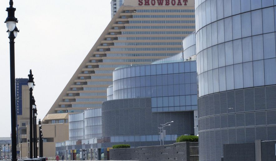 This July 3, 2015 photo shows the former Showboat casino, left and the former Revel casino, right, on the Atlantic City, N.,J., Boardwalk. (AP Photo/Wayne Parry)