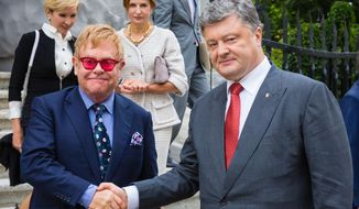 Ukrainian President Petro Poroshenko, right, and Elton John shake hands during their meeting in Kiev, Ukraine, Ukraine, Saturday, Sept. 12, 2015. (AP Photo/Mikhail Palinchak, Pool)