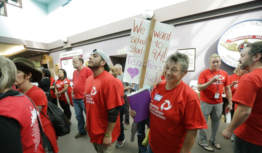 Margaret Gingrich, a second-grade teacher at Montlake Elementary school, carries a picket sign as she and other members of the Seattle Education Association, the union that represents striking teachers from the Seattle School District, file into a meeting hall, Tuesday, Sept. 15, 2015, in Seattle to discuss a tentative contract agreement that was reached with the district Tuesday morning, the fifth day of the strike. (AP Photo/Ted S. Warren)